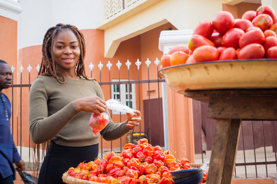 young pretty african trader feeling excited as she is packaging her tomatoes.