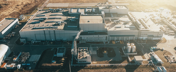 Aerial panoramic view of industrial factory or warehouse modern building in sunlight, drone point of view. Wall mural