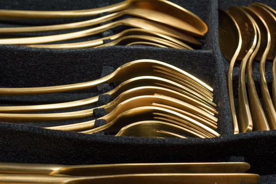 Gold colored cutlery in black cutlery tray