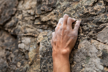 A close up shot on the fingers of a male rock climber, struggling to find a stable grip position on steep crag. Hold positions in natural stone cracks