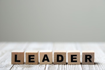 Leader word written on wood block on wooden background