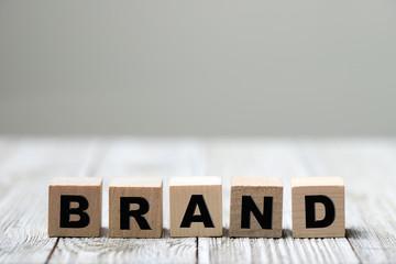 Brand word written on wood block on wooden background