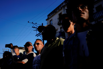 People watch Cuban and New Orleans musicians parading in downtown Havana