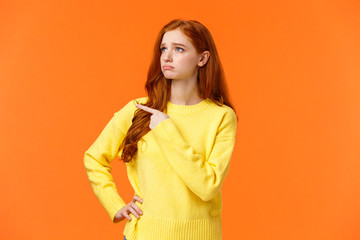 Jealous or envy sad sulking redhead girl in yellow sweater looking at desired thing, shoppaholic...