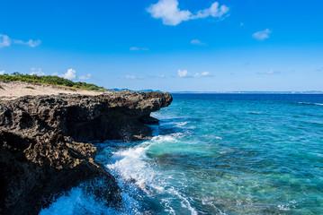 青く透き通った海の海岸沿いの岩場に波しぶきが上がっている晴れた日の久高島の風景 Wall mural