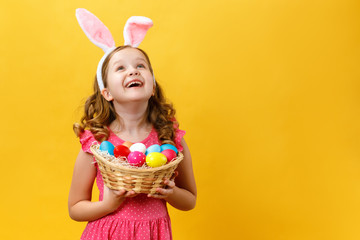 Beautiful cute little girl in Easter bunny ears holds a basket with eggs on a yellow background. The child raised his head and looks up. Copy space