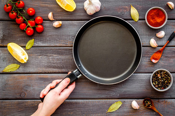 Cooking mockup. Hand hold frying pan among spices and vegetables on dark wooden desk top-down