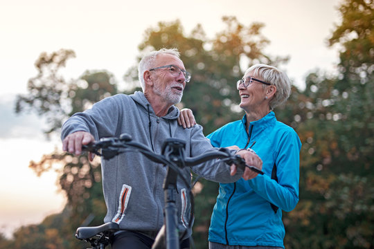 Older couple in park, he is with bicycle and she walk beside and talking