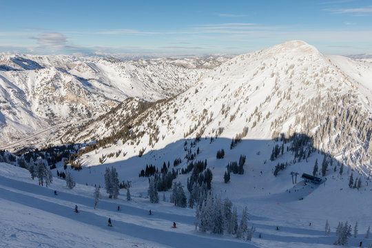 Skiers and snowboarders on slope viewed from Hidden Peak at Snowbird in Little Cottonwood Canyon in the Wasatch Range near Salt Lake City, Utah, USA.