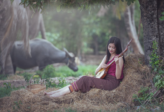 Thai woman playing folk song with Pin (Isan Guitar) traditional music instrument