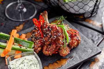 Mexican cuisine. Fried glazed chicken wings and legs with white and black sesame seeds. Green sauce. Modern serving dishes in the restaurant. background image, copy space text