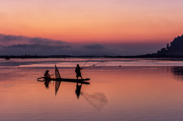 Fotobehang Koraal Silhouette of fisherman on wooden boat in nature lake with sunrise
