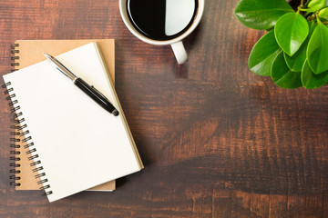 Top view of open school notebook with blank pages, Pen, Plant and Coffee cup on wooden table background. Business, office or education concept with copy space.