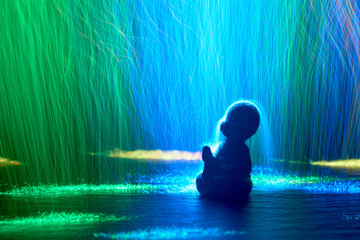 silhouette of a young buddha figure in luminous colored stripes