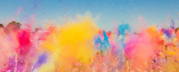 Crowd throwing bright colored powder paint in the air at Holi Festival Dahan Fotomurales
