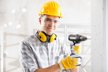 Young construction worker drilling wall indoors