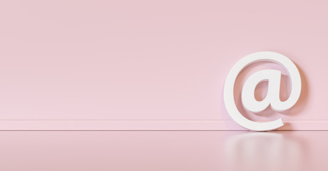 Email Icon or at sign leaning against a pink wall as a communication concept, copyspace for your individual text.