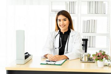 Smart young Asian female doctor in uniform smiling and looking at camera while doing paperwork at desk in office of hospital