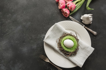 Easter table setting with white egg in nest and tulip on dark. Top view.