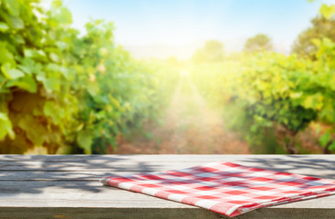 Wooden table in front of vineyard