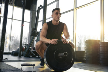 Confident. Young muscular caucasian athlete training in gym, doing strength exercises, practicing, work on his upper body with weights and barbell. Fitness, wellness, healthy lifestyle concept.