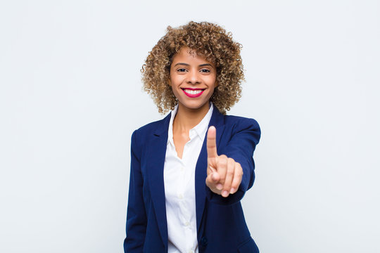 young woman african american smiling proudly and confidently making number one pose triumphantly, feeling like a leader against flat wall