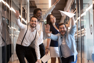 Funny multiethnic employees posing for picture in office hallway