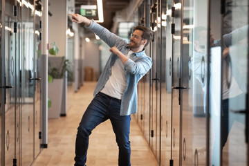 Funny happy male employee dance in office celebrating