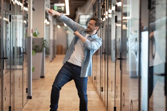 Funny happy male employee dance in office celebrating