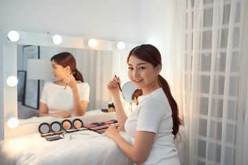 Beautiful Asian girl looking in the mirror and applying cosmetic with a brush