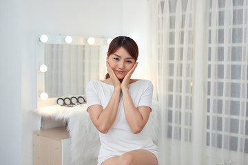 Attractive young Asian girl touching her face. Beauty & Skin care concept