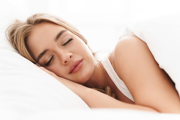 Photo of young caucasian woman sleeping while lying in bed