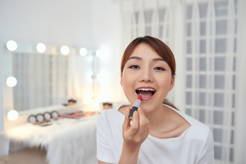 Portrait of Beautiful young Asian girl applying lipstick