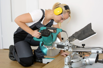 Female carpenter as a craftsman in house renovation wearing ear protection and sawing wooden board with miter saw