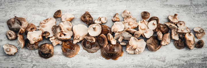 Topview panorama, lots of delicious shiitake mushrooms on wooden table