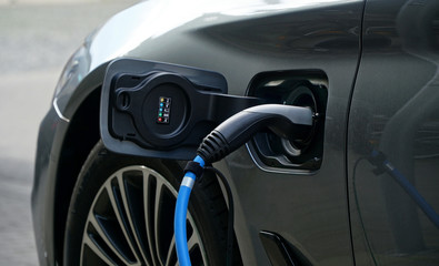 Electric or hybrid car refueling electricity at a charging station