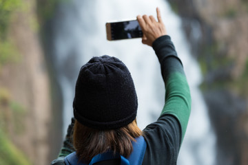 Woman taking photo waterfall in forest by smartphone