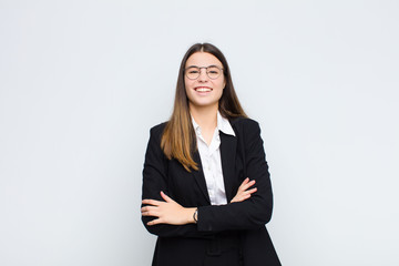 young businesswoman looking like a happy, proud and satisfied achiever smiling with arms crossed against white wall