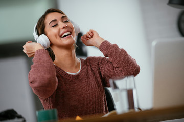 Beautiful woman in office listening music. Businesswoman relaxing, singing and dancing at her work place.