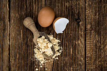 Old wooden table with fresh Powdered Eggs (close-up shot; selective focus)