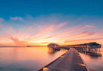 Wall Mural - Sunset on Maldives island, luxury water villas resort and wooden pier. Beautiful sky and clouds and beach background for summer vacation holiday and travel concept