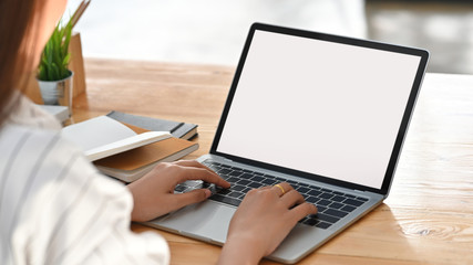 Close-up image of beautiful business woman sitting at the wooden work desk and typing on the white blank screen laptop keyboard.