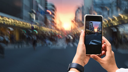 Close up image of woman hands taking a photo by use her smartphone  at dusk on pedestrian crossing.