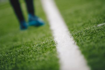 Sports grass field pitch and white sideline. Sports player walking in the blurred background