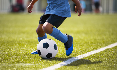 African American young boy playing soccer in a stadium pitch. Child running with soccer ball along the field white sideline. Junior soccer background