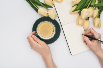 cropped view of woman writing in blank notebook with pen near tulips and fresh coffee isolated on white