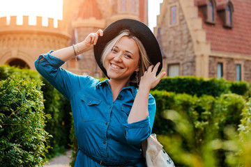 Portrait of a young beautiful fashionable happy woman posing in the street against the background of the medieval Old town.