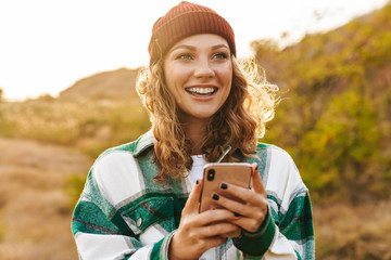 Image of joyful young woman holding cellphone while walking outdoors Fotomurales