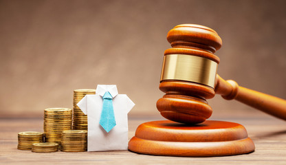 Businessman in shirt and tie with stack of coins and judge gavel on brown background. Concept of business sentence or non-payment of taxes.
