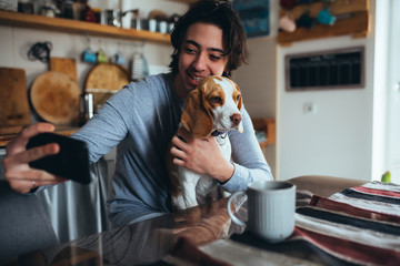 young man with his dog taking picture in kitchen at home, morning scene